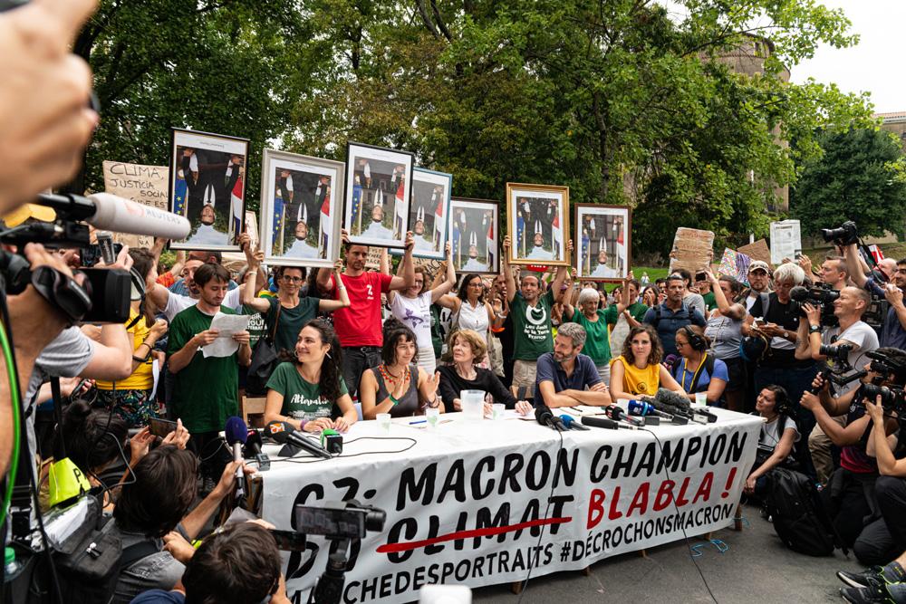 Militant·es entourés de journalistes internationaux, au fond des portraits retournés