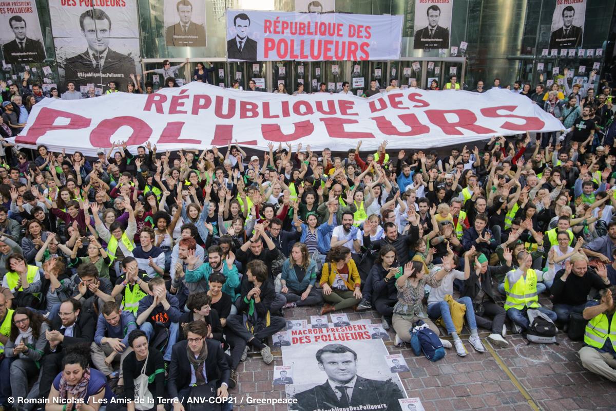 2030 activistes assis sur une place de la Défence, immense banderole dénoncant la république des pollueurs
