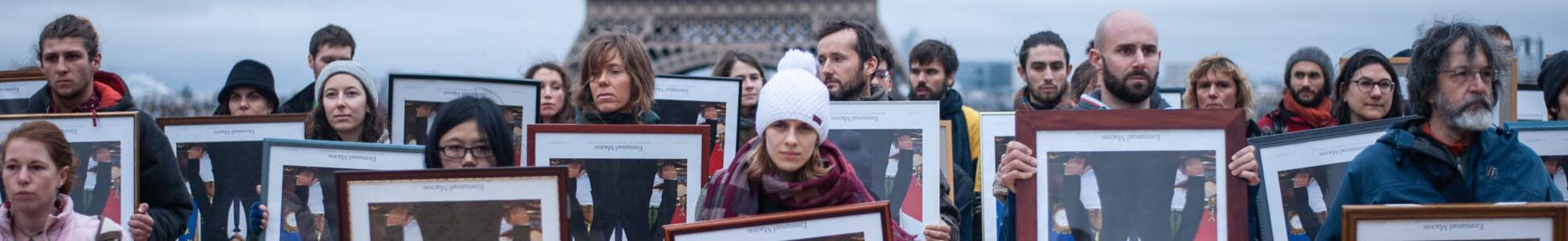 Des activistes brandissent 100 portraits présidentiels devant la Tour Eiffel, symbole de la COP21