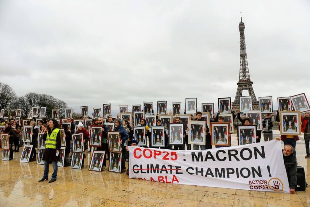 Personnes qui portent des portraits d'Emmanuel Macron devant la tour Eiffel. Banderole : COP25, Macron blabla champion