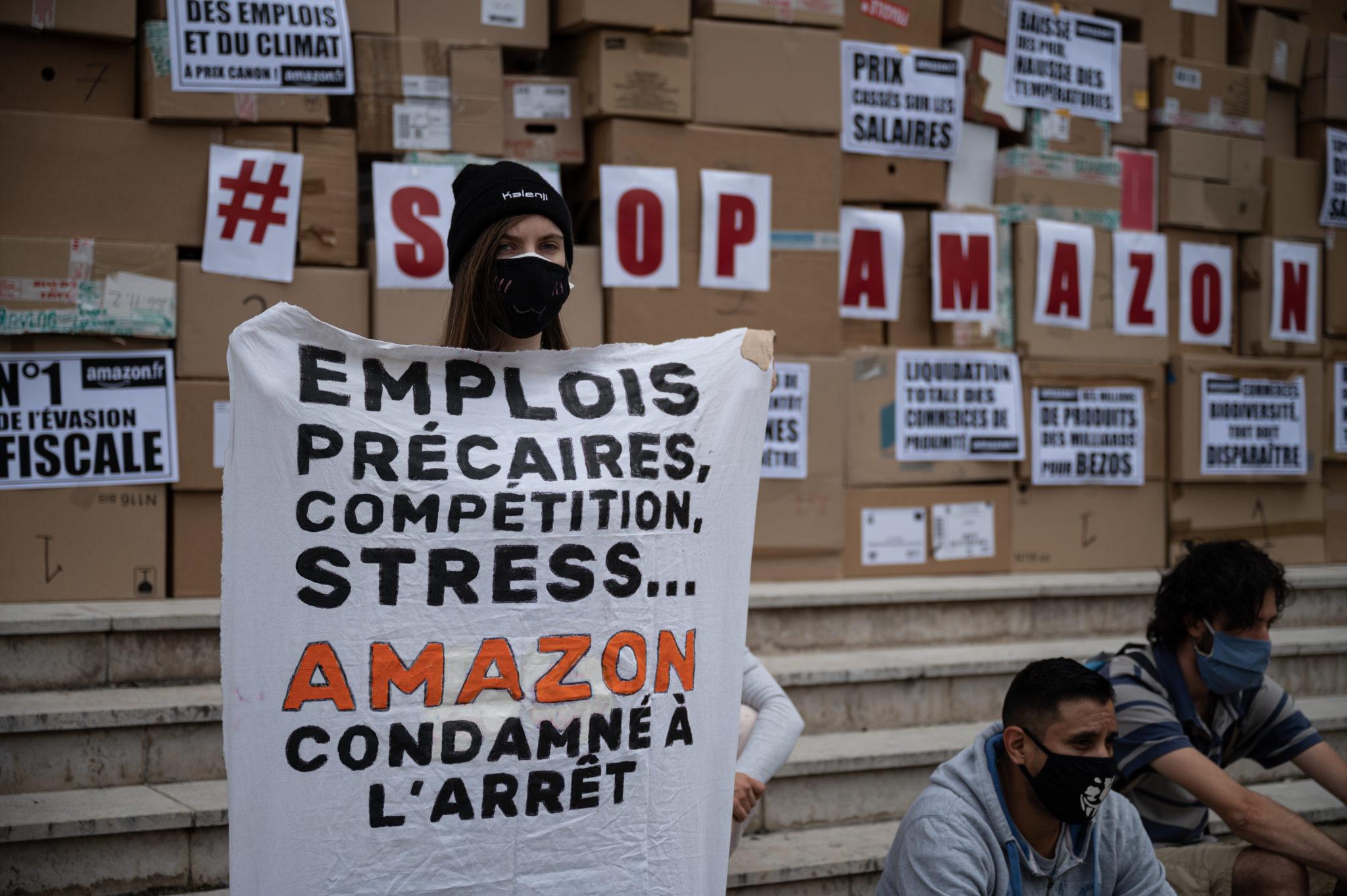 Des militants en action devant des cartons Stop Amazon